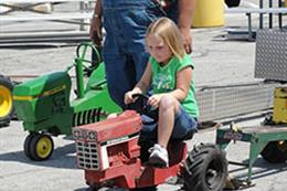 A girl pedals a tractor during the Pedal Tractor Pull.